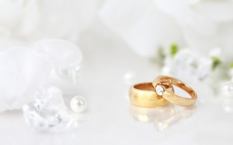 Wedding still life with beautiful golden rings and bouquet