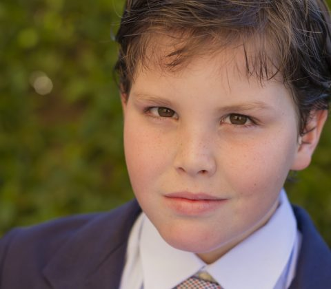 Color portrait of ten year old boy dressed in dark blue suit and tie for his first communion with green leaves background.
