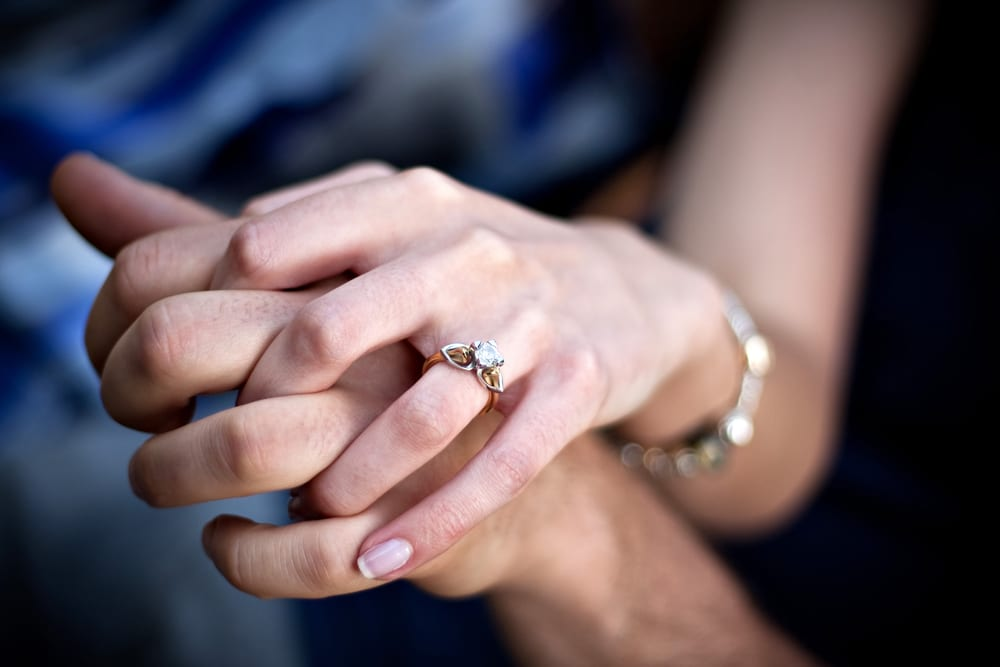Close up of a young couples hands and diamond engagement ring with platinum and gold accents. Shallow depth of field.