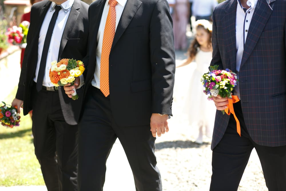gorgeous stylish elegant groom and best man holding colorful bouquets