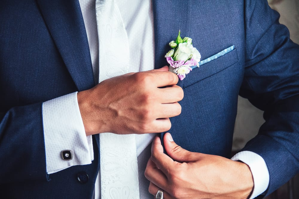 groom adjusts his boutonniere of pink flowers close up