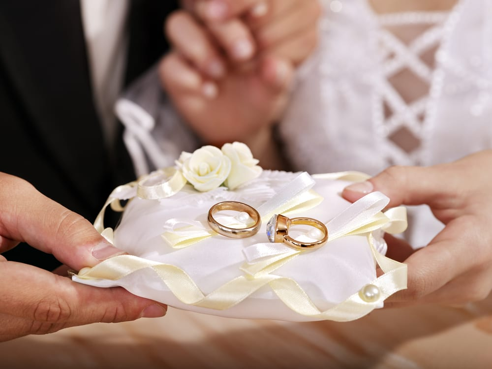Hand holding pillow with wedding ring.
