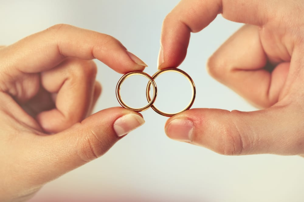 Woman and man holding wedding rings, close-up