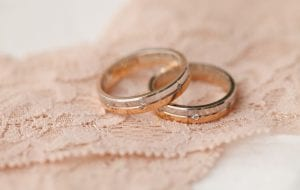 two wedding rings on pink lace